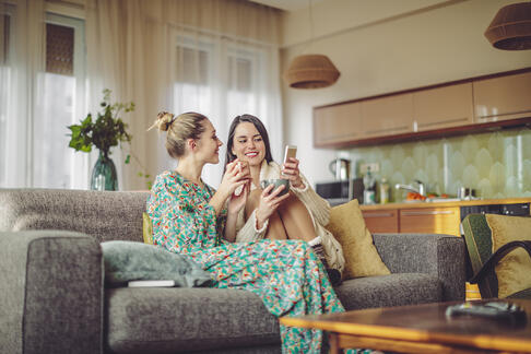 South Florida sisters shopping on phone in living room