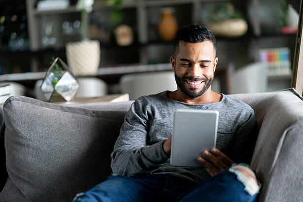 hispanic guy on couch looking at tablet