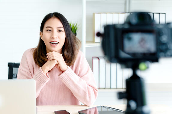 young asian american girl at desk sitting in front of camera