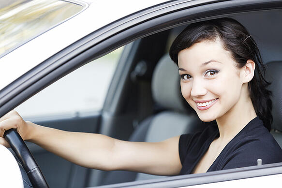 young woman with dark hair driving silver car
